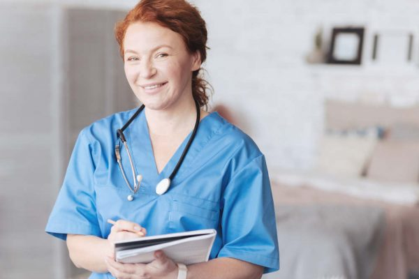 Positive attitude to work. Waist up shot of an excited caregiver with a stethoscope looking into the camera with a cheerful smile on her face and taking notes while posing.