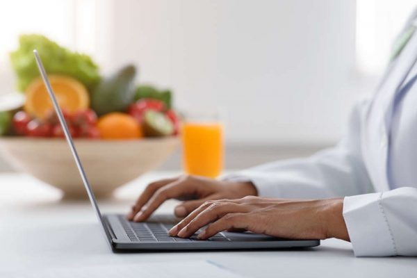 African,Woman,Nutritionist,Doctor,Working,On,Laptop,At,Office,,Bowl
