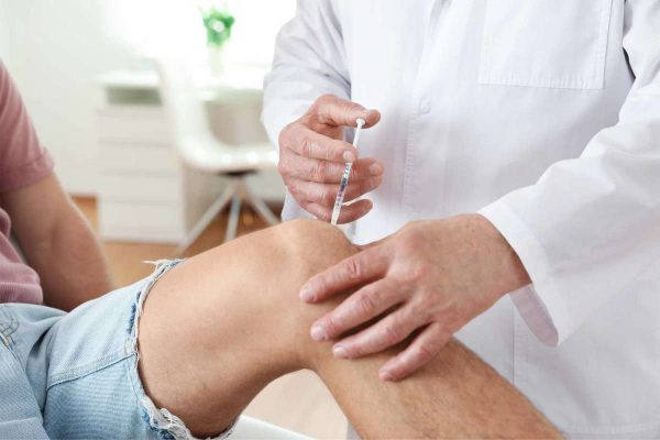 Doctor giving patient injection in clinic, closeup. Knee problem treatment