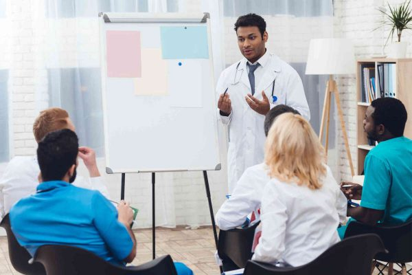 An Indian doctor advises colleagues during a medical meeting. Doctors of different nationalities are sitting next to him. On the white board hang sheets of paper.