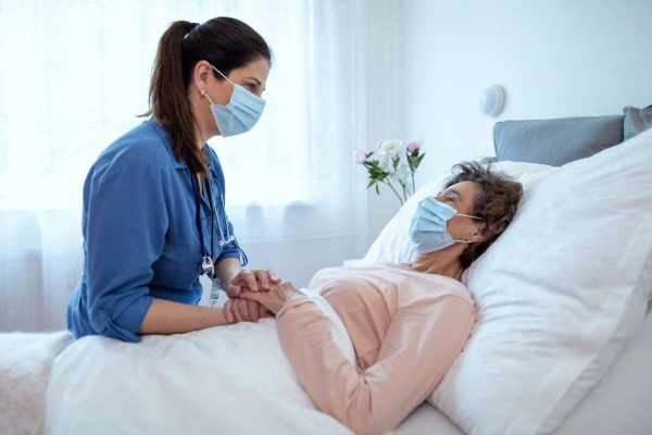 Home,Caregiver,Comforting,Senior,Female,Patient,Lying,In,Bed.,Side