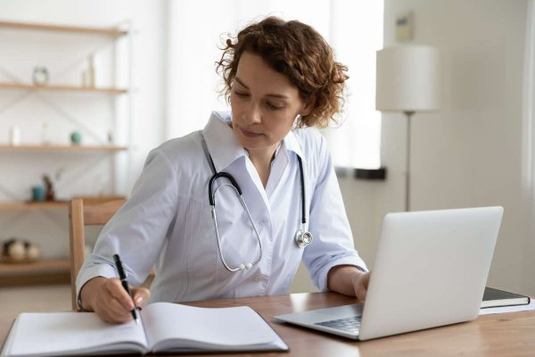 Serious,Female,Doctor,Using,Laptop,And,Writing,Notes,In,Medical