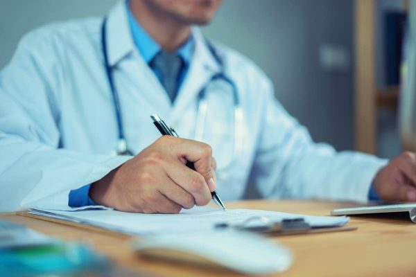 Doctor with Stethoscope clipboard and Laptop on desk,working in hospital writing a prescription, Healthcare and medical concept,test results in background,health care business graph