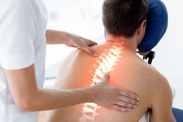 Digital,Composite,Of,Highlighted,Spine,Of,Man,At,Physiotherapy