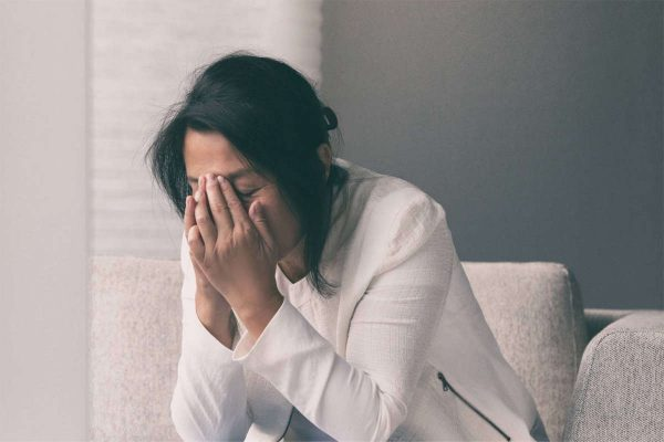 Coronavirus COVID-19 impact on retail businesses shut down causing unemployment financial distress. Depressed crying business woman stressed with headache.